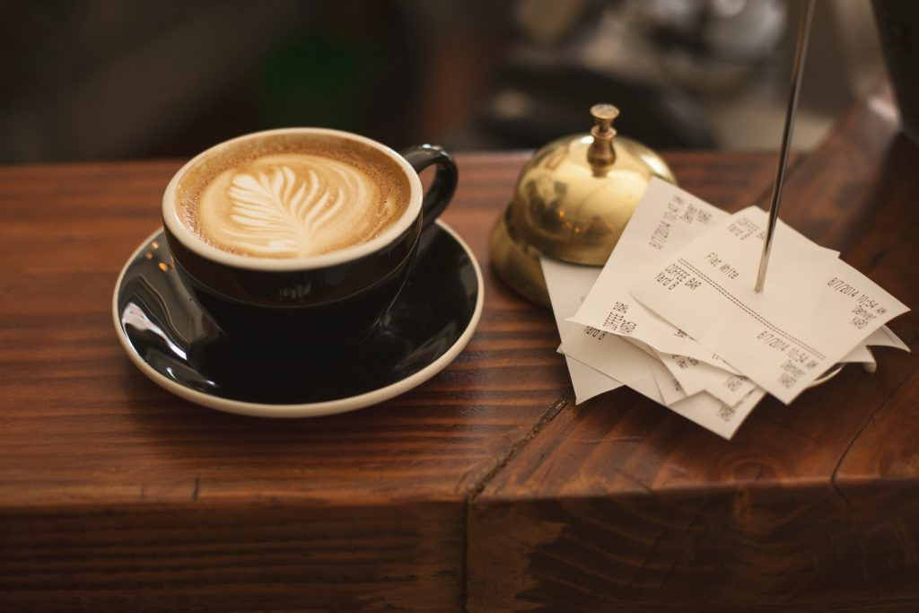 Cup of coffee next to table bell and purchase receipts