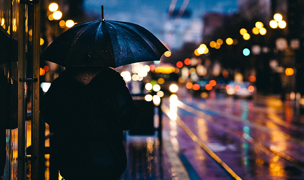 man standing under umbrella on rainy night in the city