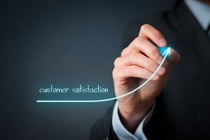 business man's hand drawing upward trend in customer satisfaction