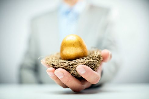 Golden nest egg in a business man's hand